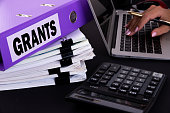 Text, word Grants is written on a folder lying on documents on an office desk with a laptop and a calculator. Business concept.