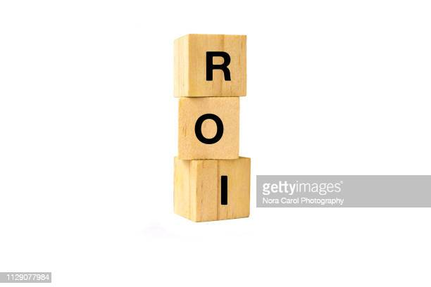 roi text written on wooden block - return on investment stock pictures, royalty-free photos & images