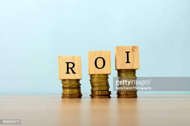 roi text written on wooden block with stacked coins - rinviare la palla foto e immagini stock