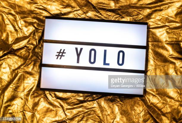 text yolo on white illuminated board you only live once concept - yolo stock-fotos und bilder