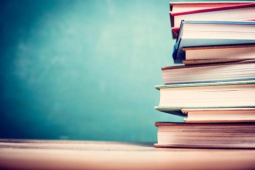 Textbooks on wooden school desk with chalkboard. 1009498682
