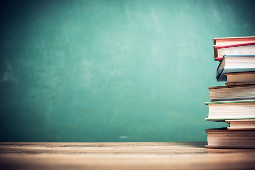 Textbooks on wooden school desk with chalkboard. 1033277722