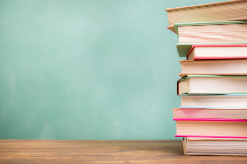 Textbooks stacked on school desk with chalkboard background. 638383032
