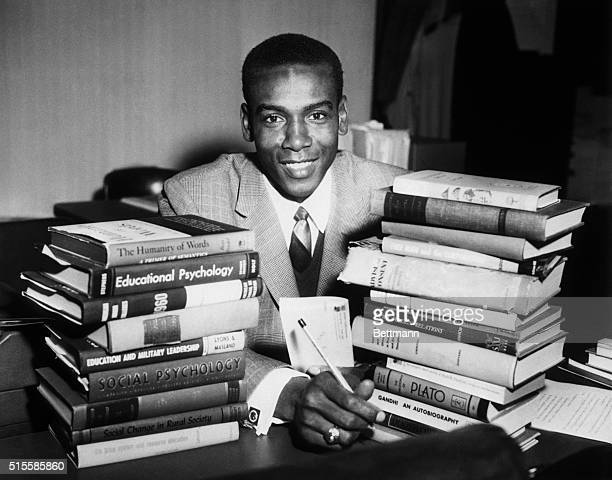 Textbooks surround Chicago Cubs star shortstop Ernie Banks as he attends class at the University of Chicago where he is taking night courses in...
