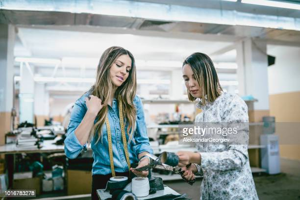 Textile Factory Colleagues Cutting Tape In Workshop