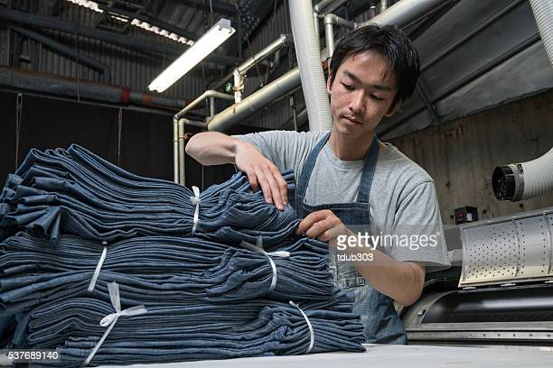 textile industry worker counting garments before shipping - textile factory stock photos and pictures
