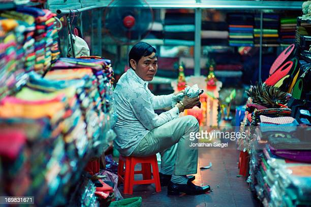 CONTENT] Textile merchant selling colorful fabric in a small shop in Cambodia