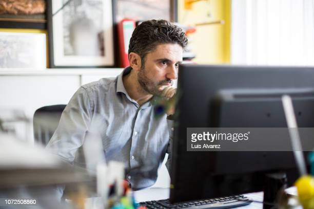 textile shop owner working at his desk - concentration stock pictures, royalty-free photos & images