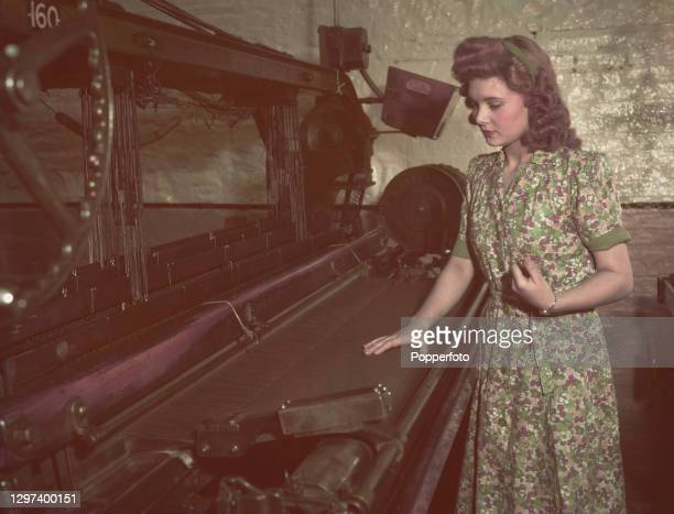 Textile worker Doreen Kerfoot works on a power loom at Scotts Mills factory in Bradford, Yorkshire, England in October 1947.
