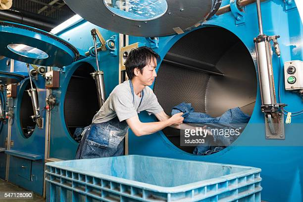 textile worker looking confident in a large washing plant - textile factory stock photos and pictures