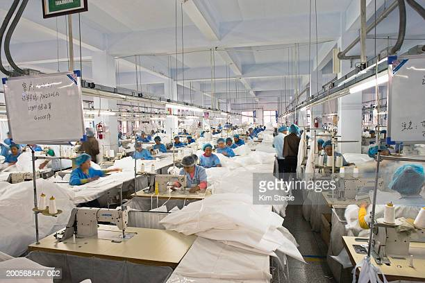 textile workers in long rows at sewing machines making clean suits. - fábrica têxtil imagens e fotografias de stock