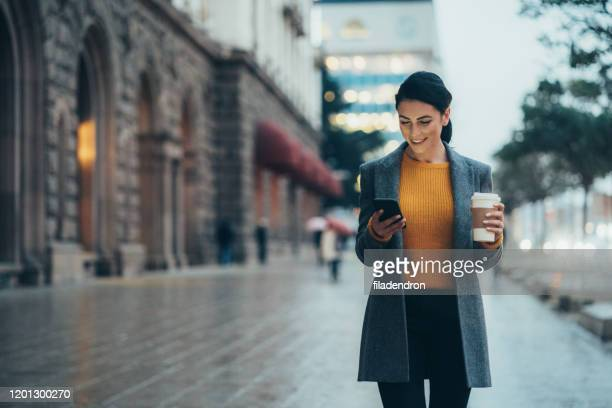 texting in the city - using phone stock pictures, royalty-free photos & images