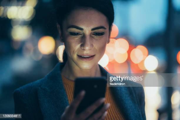 texting in the city - adulto de idade mediana imagens e fotografias de stock