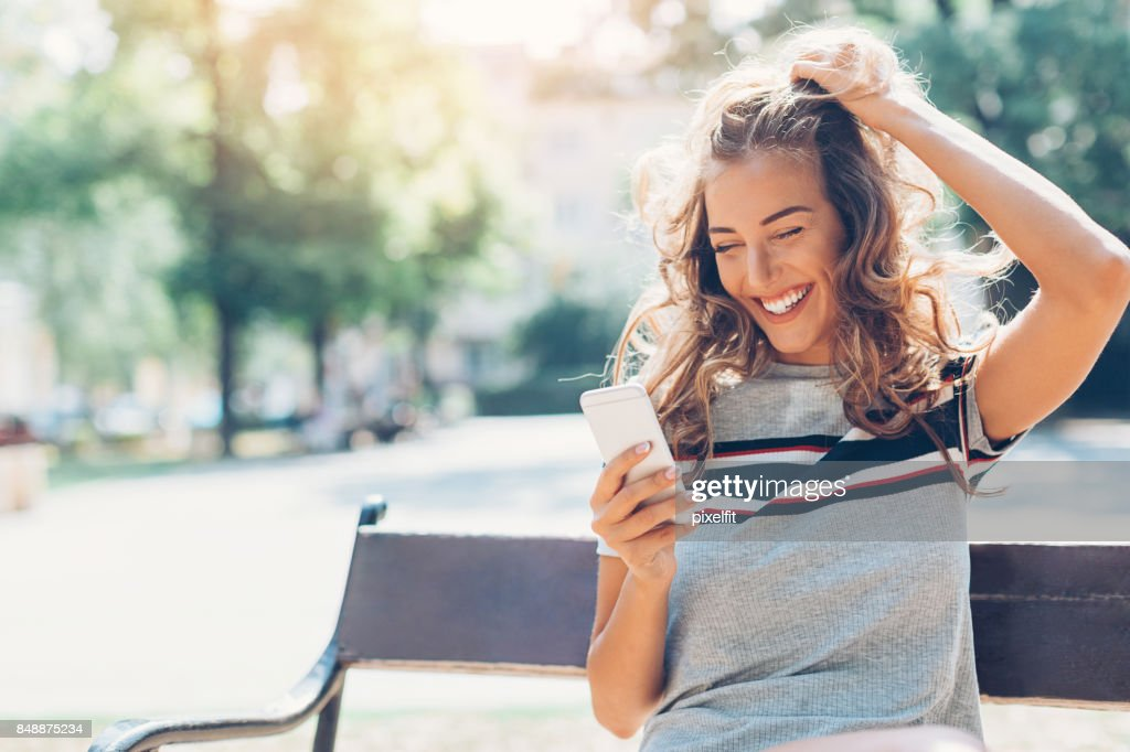 Texting in the park : Stock Photo
