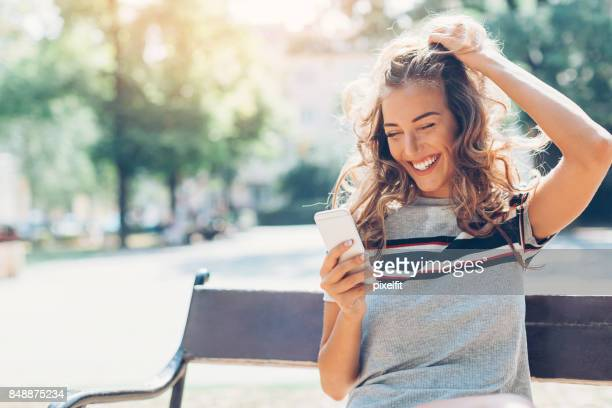 texting in the park - candid forum stock pictures, royalty-free photos & images