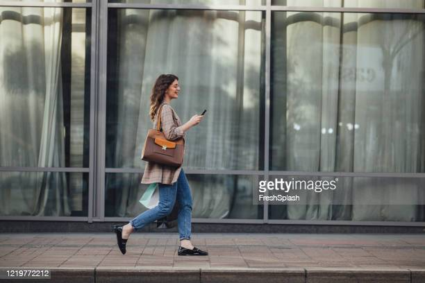 mensajes de texto sobre la marcha: mujer con bolsas de compras enviando mensajes de texto mientras camina por la calle - mujeres de mediana edad fotografías e imágenes de stock