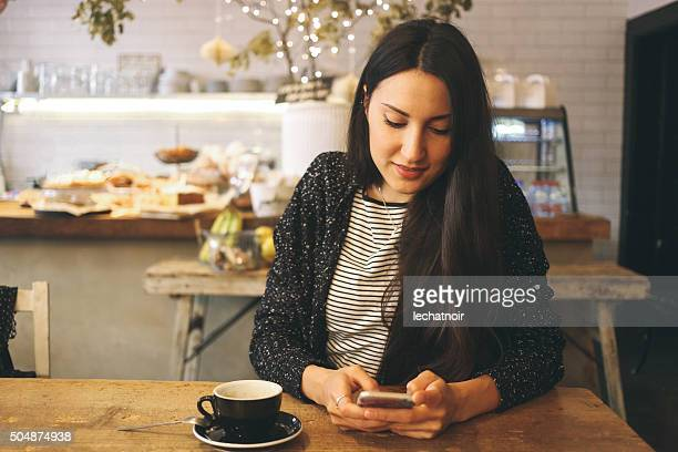 Texting on the smartphone on the coffee break