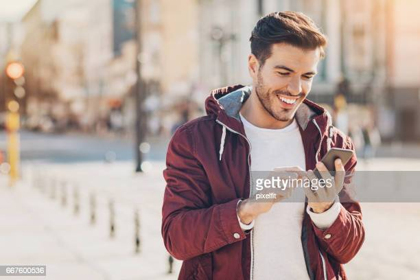 texting on the street - mid adult men stock pictures, royalty-free photos & images