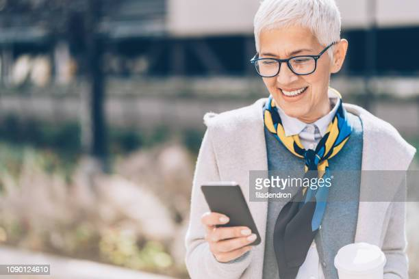texting outdoors - one mature woman only stock pictures, royalty-free photos & images