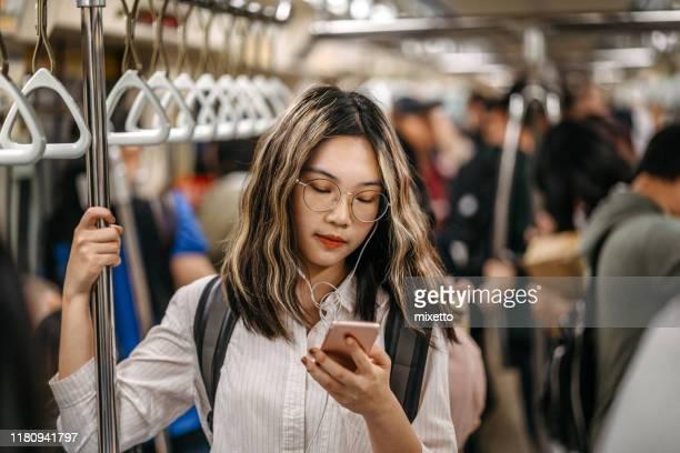 地下鉄で学校に行く途中で彼女の友人にテキストメッセージ - 内部 ストックフォトと画像