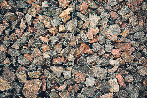 Texture for the background backdrop freely lying stone supported by a metal mesh. Technology of construction of fences from natural materials. Element of landscape design for architecture 1143349913