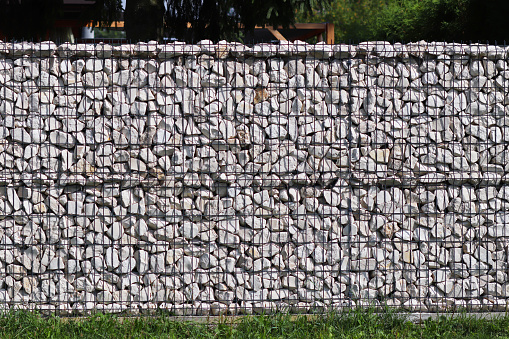 Texture for the background of a backdrop of a freely lying stone supported by a metal mesh. Technology of construction of fences from natural materials. Element of landscape design for architecture 1001339038