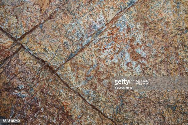 Textured grey rock background with rust iron ore and quartz veins
