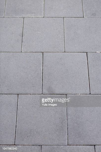 Textured grey square tiles for paving
