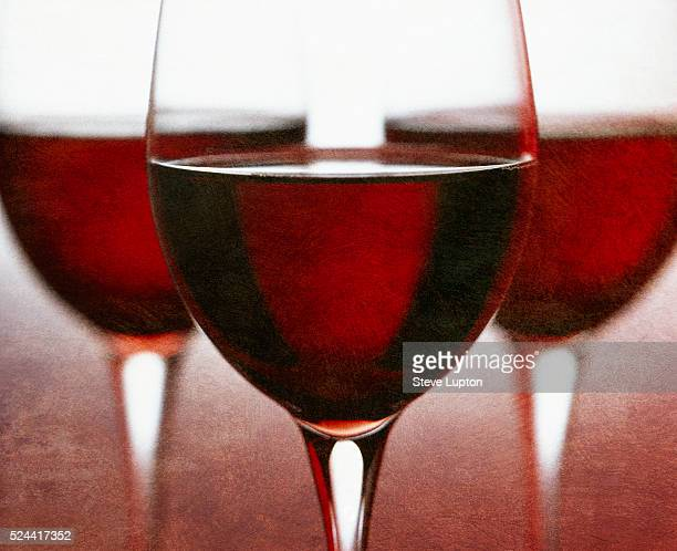 Three stemmed glasses of rich red wine