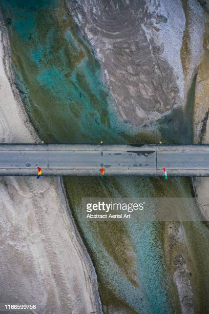 textures of a river and a bridge as seen from above, dolomites, italy - flussbett stock-fotos und bilder