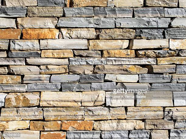 textures of a wall of stone in rows of multiple colors - stone wall stock pictures, royalty-free photos & images