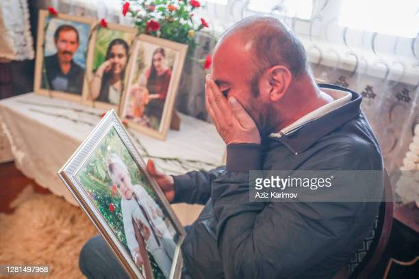Teymur Sarkarov holds relavtives portrait and crying sits inside his home on October 21, 2020 in Ganja, Azerbaijan during the ongoing military...