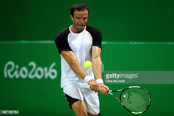 Teymuraz Gabashvili of Russia plays a backhand against Radu Albot of Moldova in their singles match on Day 2 of the Rio 2016 Olympic Games at the...