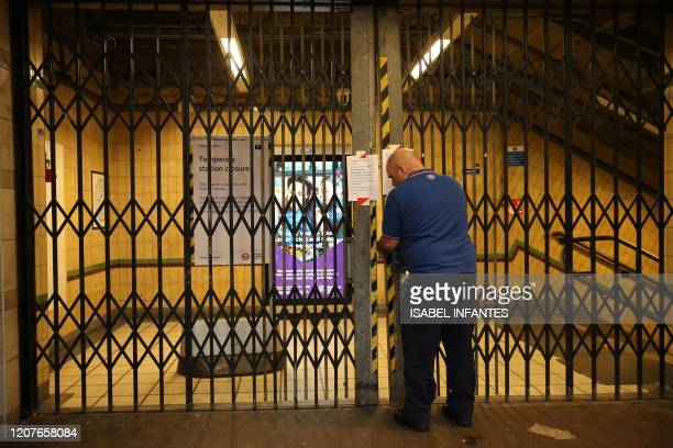 A TfL worker closes the gates at Barbican Underground station as it is temporarily closed in London on March 19 2020 as public transport services in...