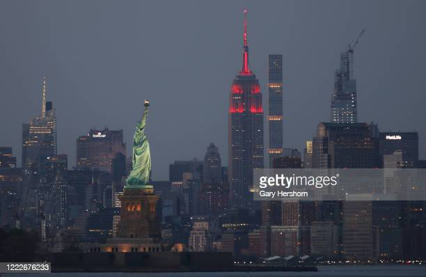 Th Empire State Building sits behind the Statue of Liberty in New York City as it continues to honor COVID19 healthcare workers by being lit in red...