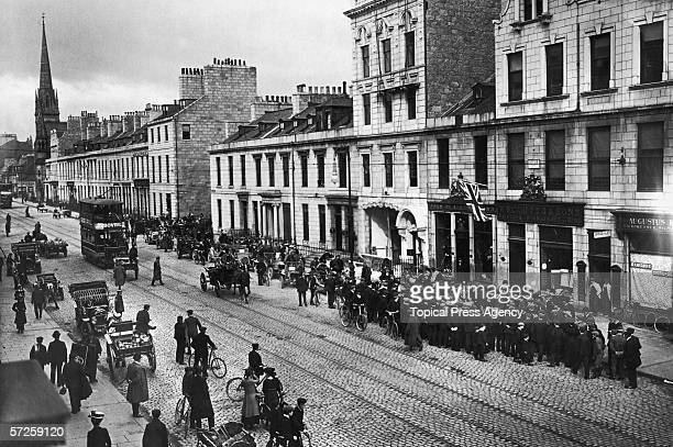 Tha Scottish Reliability Trail motoring event attracts onlookers in a street in Inverness 27th June 1907