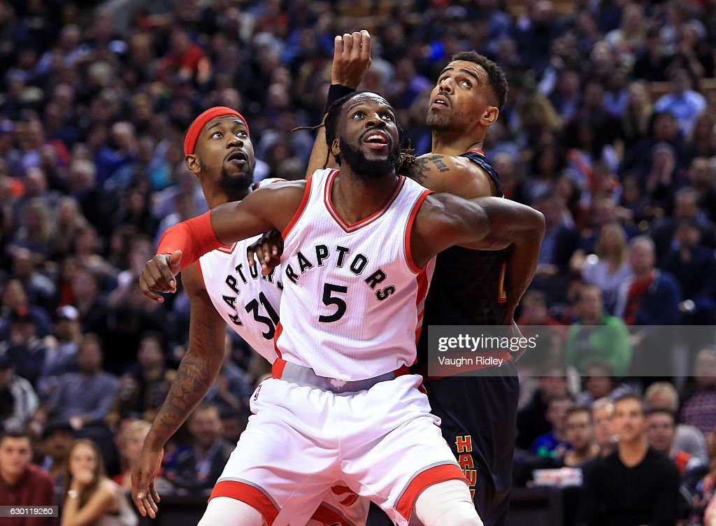Thabo Sefolosha #25 of the Atlanta Hawks battles for a rebound with Terrance Ross #31 and DeMarre Carroll #5 of the Toronto Raptors defends during the second half of an NBA game at Air Canada Centre on December 16, 2016 in Toronto, Canada.