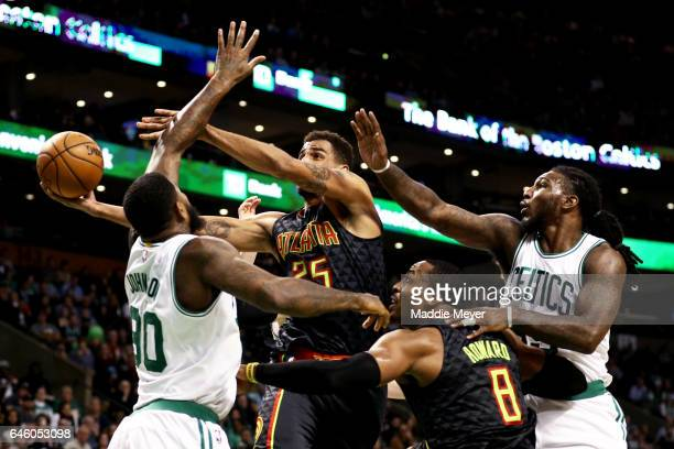 Thabo Sefolosha of the Atlanta Hawks looks for a shot against Amir Johnson of the Boston Celtics while Dwight Howard of the Hawks defends Jae Crowder...
