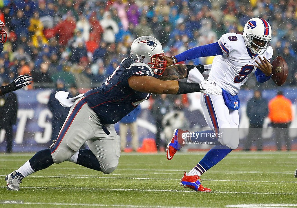 Thad Lewis #9 of the Buffalo Bills fumbles the ball while being ran down by Sealver Siliga #71 of the New England Patriots in the first quarter during the game at Gillette Stadium on December 29, 2013 in Foxboro, Massachusetts.