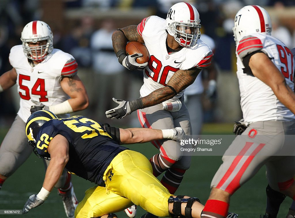 Thaddeus Gibson #90 of the Ohio State Buckeyes tries to avoid the tackle of Stephen Schilling #52 of the Michigan Wolverines after a fourth quarter interception on November 21, 2009 at Michigan Stadium in Ann Arbor, Michigan. Ohio State won the game 21-10.