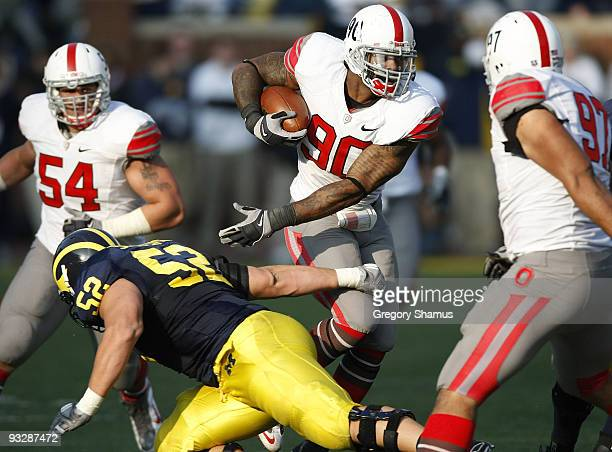 Thaddeus Gibson of the Ohio State Buckeyes tries to avoid the tackle of Stephen Schilling of the Michigan Wolverines after a fourth quarter...