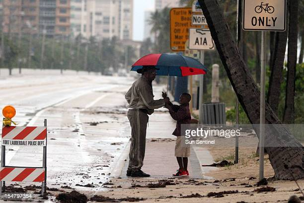 Thaddeus Hamilton, of Sunrise, left, holds an umbrella for his grandson Christian Hamilton of Lauderhill, as they check out sand and debris onto the...