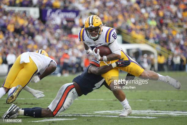 Thaddeus Moss of the LSU Tigers is tackled by Noah Igbinoghene of the Auburn Tigers during the second half at Tiger Stadium on October 26 2019 in...