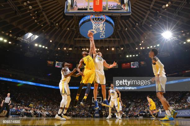 Thaddeus Young of the Indiana Pacers and Zaza Pachulia of the Golden State Warriors go for a rebound during the game on March 27 2018 at ORACLE Arena...