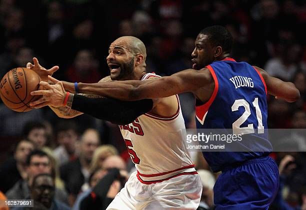 Thaddeus Young of the Phildelphia 76ers tries to knock the ball away from Carlos Boozer of the Chicago Bulls at the United Center on February 28 2013...