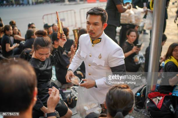 Thai actor Atichart Chumnanon gives out food and drinks to people waiting for the last funeral procession of the late Thai King Bhumibol Adulyadej on...