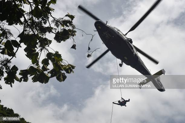 A Thai Airforce worker drops in by helicopter into a clearing in the forest near a possible overground opening to the Tham Luang cave at the Khun Nam...