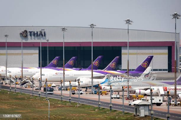 Thai Airways aircraft are parked on the tarmac at Suvarnabhumi Airport in Bangkok on March 25, 2020 as the airline suspended international flights...