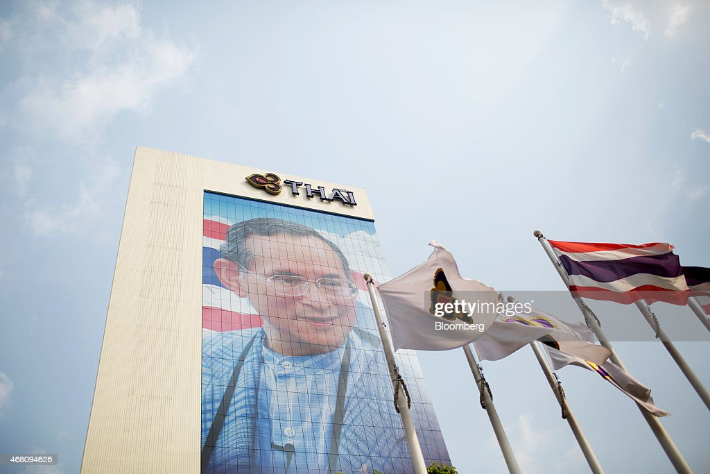 Thai Airways International Pcl, left, and Thai national flags fly in front of an image of Bhumibol Adulyadej, king of Thailand, at the carrier's headquarters in Bangkok, Thailand, on Wednesday, March 25, 2015. Thai Airways, which has posted annual losses the past two years, expects to show another loss this year before returning to profitability in 2016 by selling aircraft, dropping routes and cutting other costs. Photographer: Brent Lewin/Bloomberg via Getty Images