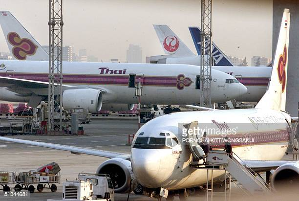 Thai Airways International plane sits in a loading zone at Bangkok airport 14 March 2000 meanwhile Thailand's cabinet approved a partial...
